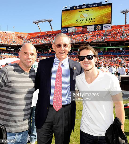 American Idol winner Kris Allen poses with Miami Dolphins owner Stephen Ross and Cirque du Soleil CEO Guy Laliberte on the sidelines before the start...