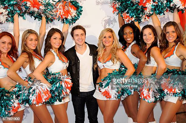 American Idol winner Kris Allen poses with the Miami Dolphin cheerleaders on the the orange carpet before the start of the NFL game between the...