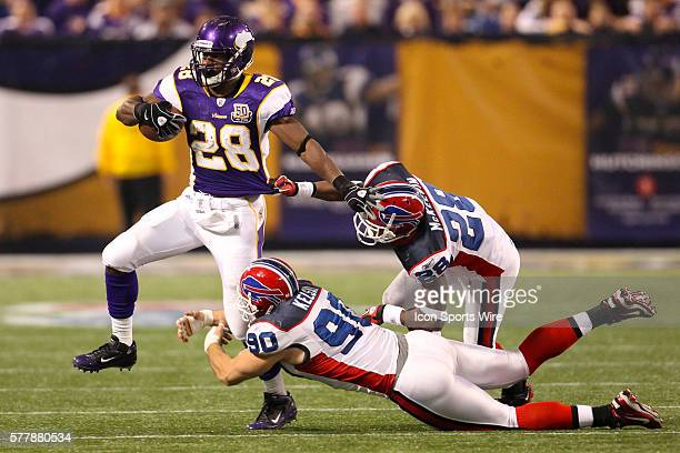 Minnesota Vikings running back Adrian Peterson runs with the ball as he is tackled by Buffalo Bills cornerback Leodis McKelvin and linebacker Chris...