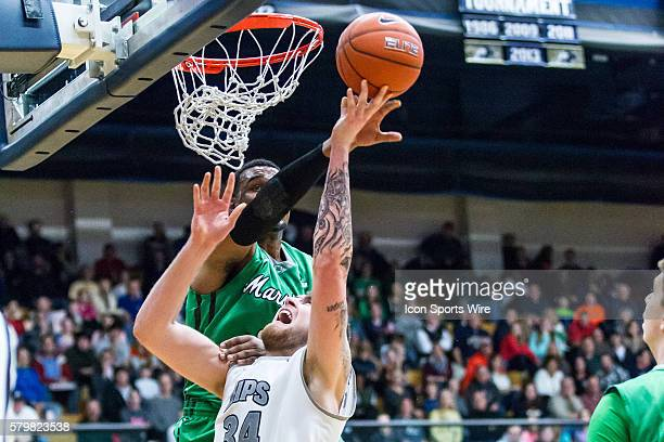 Akron Zips C Pat Forsythe is fouled by Marshall Thundering Herd F Jay Johnson during the game between the Marshall Thundering Herd and Akron Zips at...