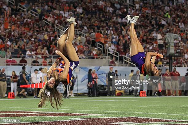 Clemson Tigers cheerleaders go flying thru the air mid flip after the Tigers scored a touchdown during the 2014 Russell Athletic Bowl between the...