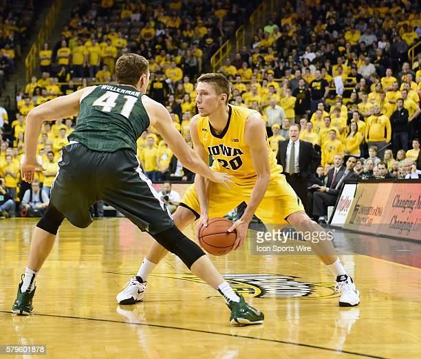 Iowa Hawkeyes forward Jarrod Uthoff looks for an open lane while defended by Michigan State Spartans forward Colby Wollenman during a Big Ten...