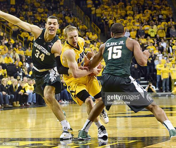 Iowa Hawkeyes guard Mike Gesell guarded by Michigan State Spartans forward Gavin Schilling and Michigan State Spartans forward Marvin Clark in the...