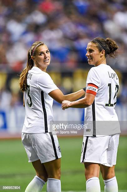 United States of America forward Alex Morgan and midfielder Carli Lloyd look back during the first half of a women's exhibition game between the US...