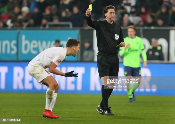 Soccer Bundesliga FC Augsburg FC Schalke 04 15th matchday in the WWKArena Referee Manuel Gräfe shows Augsburg's Rani Khedira the yellow card Photo...