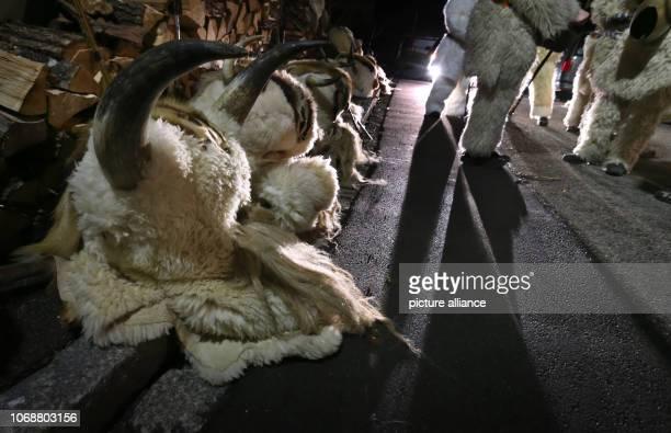 December 2018, Bavaria, Burgberg: Klausen masks lie on the street before the beginning of the Klausentreiben. In the Klausentreiben young men,...