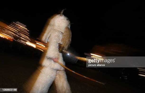 December 2018, Bavaria, Burgberg: Klausen walk through the village with rods in their hands. In the Klausentreiben young men, disguised with animal...
