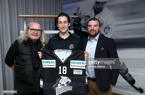 December 2018, Bavaria, Nürnberg: Brandon Buck , striker of the Thomas Sabo Ice Tigers, holds the jersey of the Spengler Cup in his hands during the...