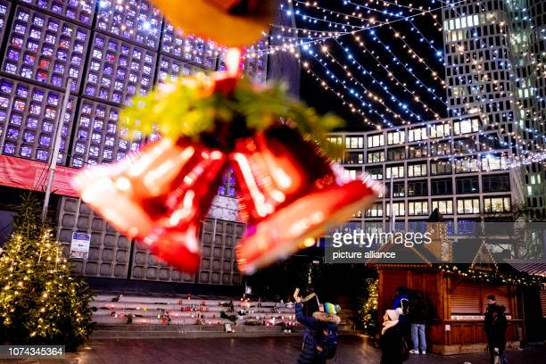 Christmas bells hang from a stand in front of the memorial for the victims of the assassination on at the Christmas market at Breitscheidplatz Two...