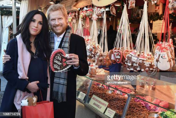 Life characters actors with silicone masks by Prince Harry and Meghan Markle of Madame Tussauds Berlin stand with a gingerbread heart with the...