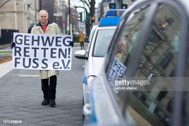 """December 2018, Berlin: Reinhard Nake from the pedestrian lobby association Fuss holds a banner with the inscription """"Gehweg sparen! Fuss e.V."""" and..."""
