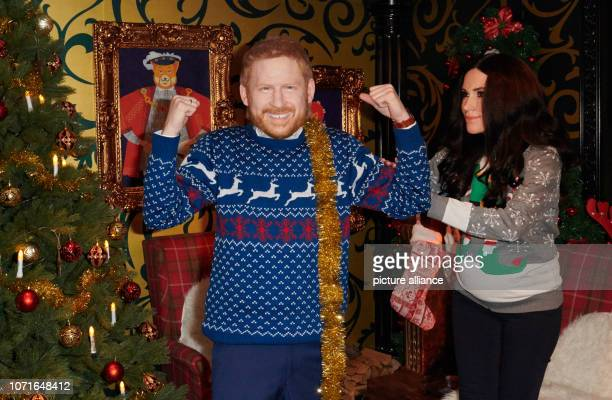 The live characters of Prince Harry and his wife Meghan play a scene in a Christmassy decorated living room at Madame Tussauds The wax masks are worn...