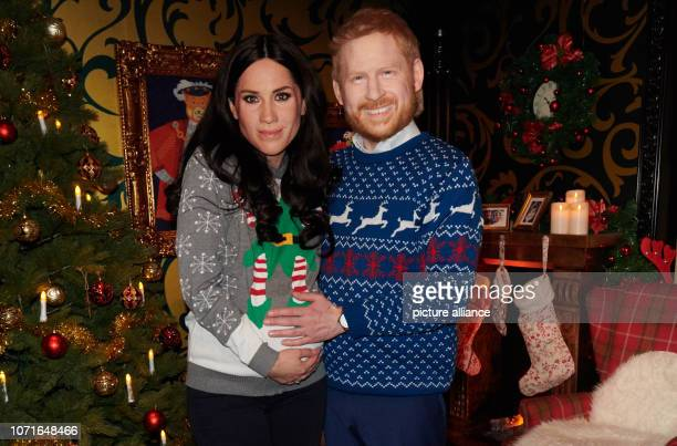 The live figures of Prince Harry and his wife Meghan stand in a Christmassy decorated representation of a living room in Madame Tussauds The wax...