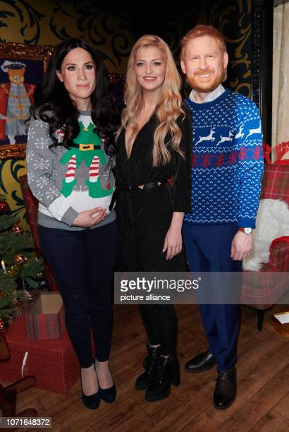 The pregnant live figure Duchess Meghan the real Xenia Princess of Saxony and the live figure of Prince Harry stand in a Christmassy decorated...