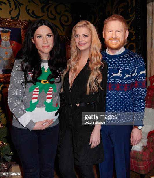 The pregnant live figure of Duchess Meghan the real Xenia Princess of Saxony and the live figure of Prince Harry stand in a Christmassy decorated...