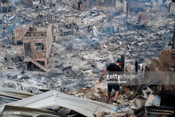 Residents of the poor quarter Educandos go through the ashes of their destroyed houses after a major fire Around 600 wooden stilt houses were...