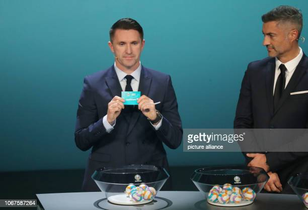The Irishman Robbie Keane shows the lot of Germany in the draw for the qualification groups for the EM 2020 On the right is Vitor Baia from Portugal...