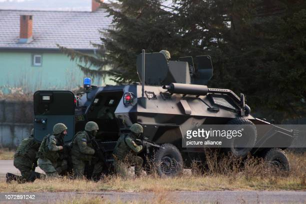 During an exercise members of a battalion of Kosovo Security Forces seek protection behind an Otokar Cobra armoured vehicle from Turkey On December...