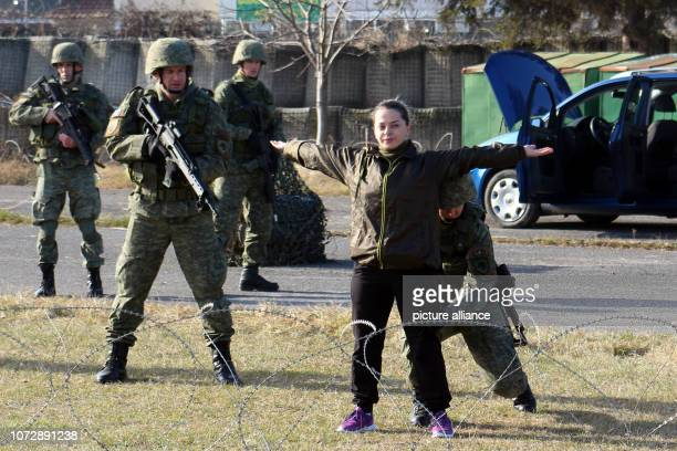 Members of a battalion of Kosovo Security Forces search a woman during an exercise On December 14 the Kosovo parliament wants to take the decision to...