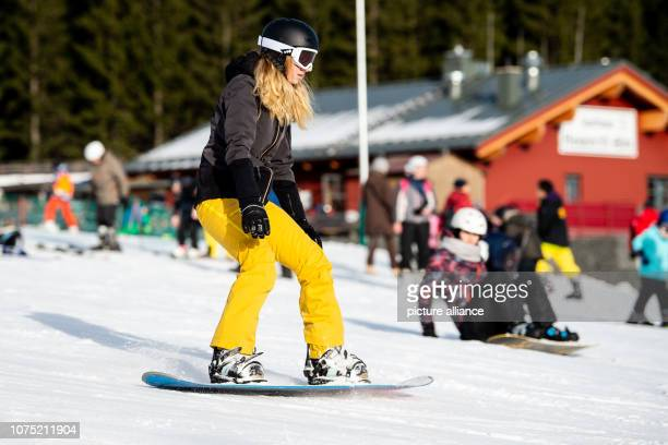 27 December 2018 Lower Saxony Braunlage A winter sportswoman rides a snowboard down a hill on a witch ride On the witch ride at Wurmberg in the Harz...