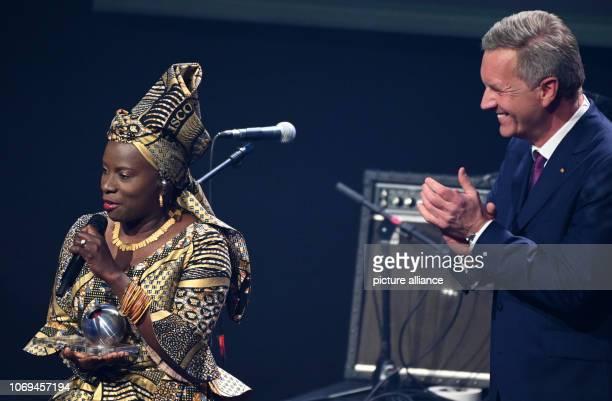 07 December 2018 North RhineWestphalia Düsseldorf Angelique Kidjo singer receives an honorary prize from former German President Christian Wulff at...