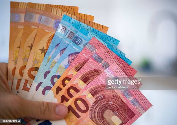 December 2018, Saxony, Dresden: ILLUSTRATION - A woman holds banknotes of 10, 20 and 50 euros in her hand . Photo: Monika...