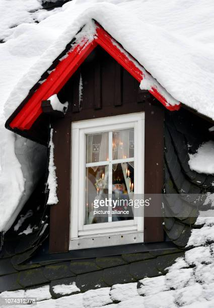 A nutcracker stands behind a snowcovered roof window in the toy village Seiffen During Advent Seiffen is considered a tourist magnet and attracts...