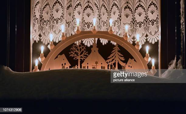 A socalled Schwibbogen with the motive of the Seiffener mountain church shines in a window of the toy village Seiffen During Advent Seiffen is...
