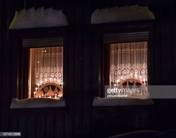 Candle arches with the motive of the Seiffener mountain church shine in a window of the toy village Seiffen During Advent Seiffen is considered a...