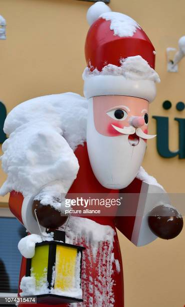 Snow covers a largerthanlife Santa Claus in the toy village of Seiffen During Advent Seiffen is considered a tourist magnet and attracts numerous...