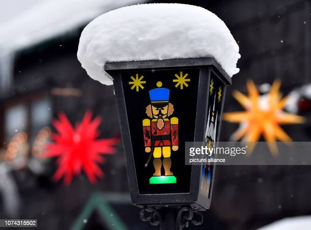 Snow lies on a lantern with traditional toy motives in the toy village Seiffen During Advent Seiffen is considered a tourist magnet and attracts...