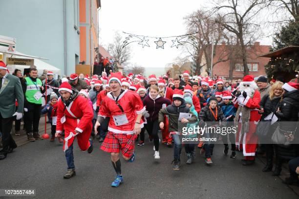 15 December 2018 Thuringia Bilzingsleben Runners in Santa Claus costumes run through the community street during the traditional Santa Claus run The...