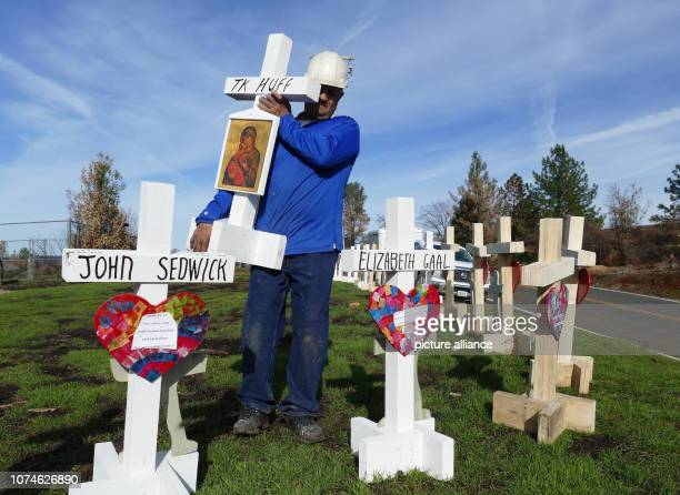 Carpenter Greg Zanis sets up wooden crosses in memory of the dead of the Camp fire in the Paradise area at the entrance to the village along the main...