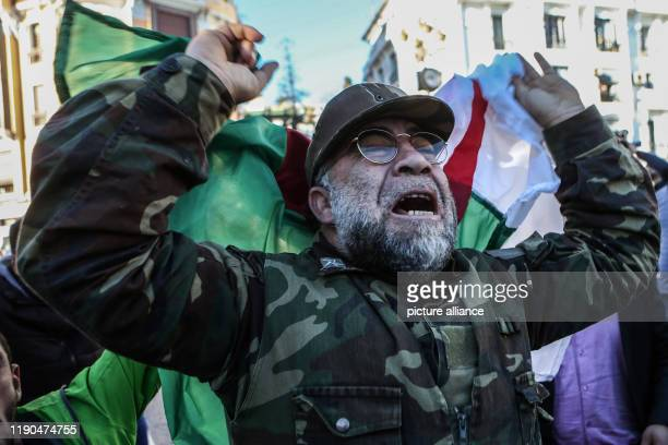 A man in a military uniform grieves as he holds the Algerian flag during the funeral of Algerian Army Chief of Staff Ahmed Gaid Salah who died Monday...