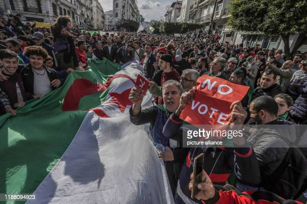 Algerian demonstrators hold a huge national flag and signs reading No vote during a demonstration against the ongoing presidential elections Photo...