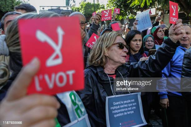 Algerian protesters hold red placard during an antigovernment demonstration to protest against a presidential election scheduled for Thursday Photo...
