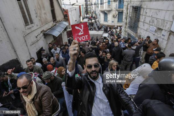 An Algerian demonstrator holds a sign reading No vote during a demonstration against the ongoing presidential elections Photo Farouk Batiche/dpa