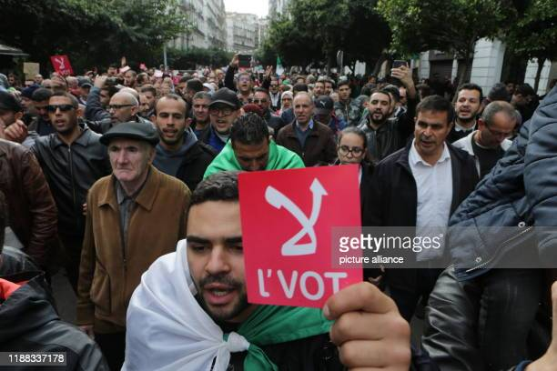 """December 2019, Algeria, Algiers: An Algerian demonstrator holds a sign reading """"No vote"""" during a protest against the newly elected President..."""