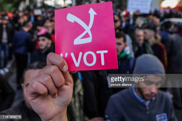 An Algerian protester holds a red placard during an antigovernment demonstration to protest against a presidential election scheduled for Thursday...