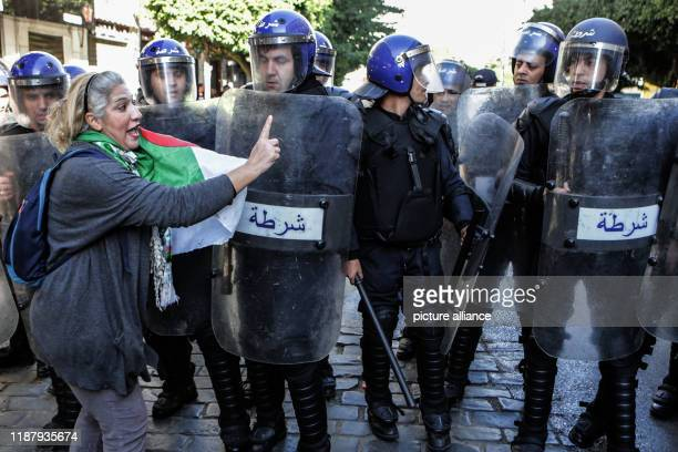 An Algerian protester talks with soldiers during an antigovernment demonstration to protest against a presidential election scheduled for Thursday...