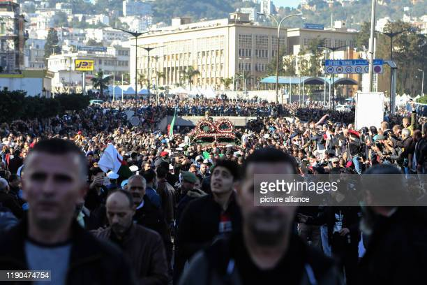 People gather around an armoured vehicle pulling the casket of Algerian Army Chief of Staff Ahmed Gaid Salah during his funeral after he died at the...
