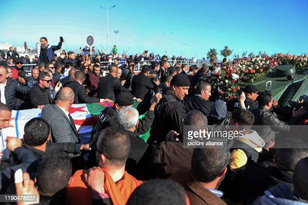 People gather around an armoured vehicle pulling the flagdraped casket of Algerian Army Chief of Staff Ahmed Gaid Salah during his funeral after he...