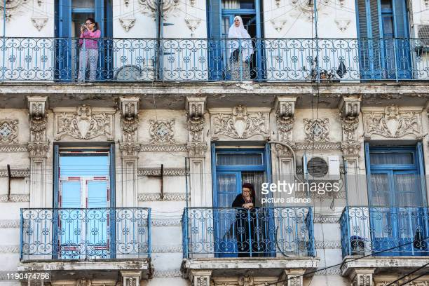 Women stand in the balconies of a residential building to watch the funeral of Algerian Army Chief of Staff Ahmed Gaid Salah who died Monday at the...