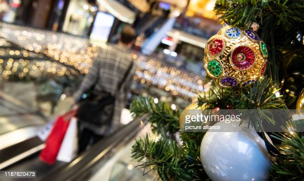 December 2019, Berlin: Customers walk past a Christmas decoration in a shopping mall. Every second consumer in Germany feels stressed during...