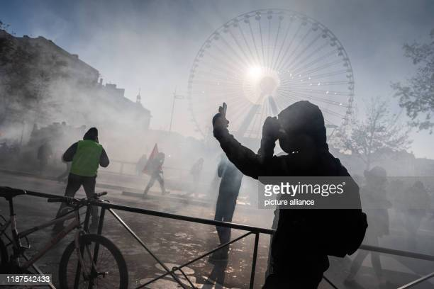 December 2019, France , Lyon: A demonstrator films himself in the haze of tear gas and pyrotechnics during a demonstration in the context of strikes...