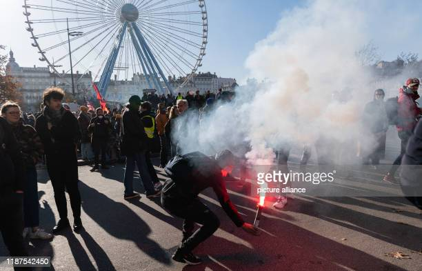 December 2019, France , Lyon: A demonstrator ignites pyrotechnics during a demonstration in the context of strikes and protests against the pension...