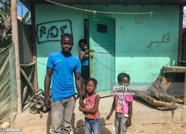 December 2019, Haiti, Croix-des-Bouquets: Frantz Charlestin, Marie France Bellefleur and their three daughters stand in front of their house in the...
