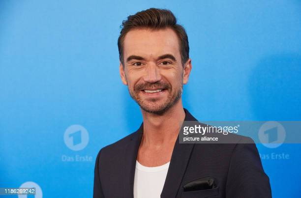 December 2019, Hamburg: Florian Silbereisen, presenter, stands in front of a logo wall at a photo shoot on the occasion of the ARD annual press...