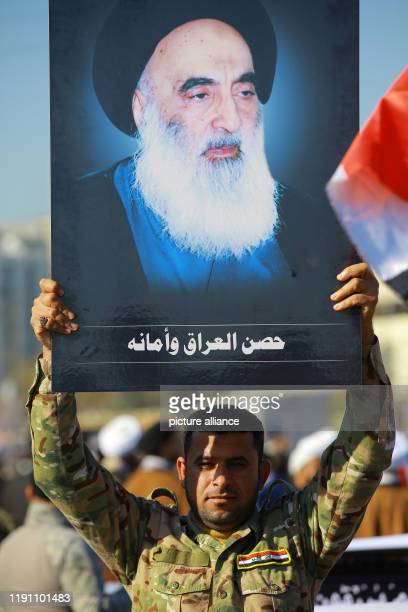 December 2019, Iraq, Baghdad: A member of Hashed al-Shaabi holds a picture of Iraq's top Shiite cleric Grand Ayatollah Ali Sistani during a...