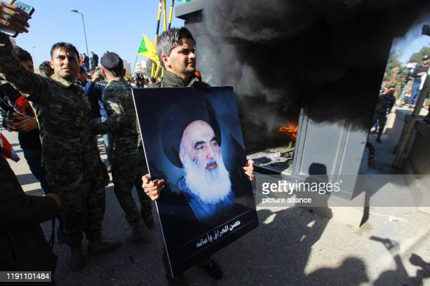 December 2019, Iraq, Baghdad: An Iraqi protester holds a picture of Iraq's top Shiite cleric Grand Ayatollah Ali Sistani during a demonstration...